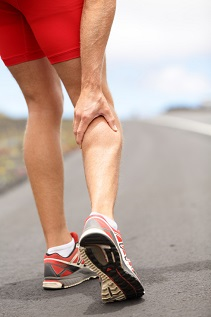 Cramps in leg calves or sprain calf on ttriathlete runner. Sports injury concept with running man.
